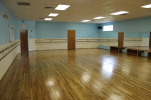 A large dance studio with blue walls and wood floors