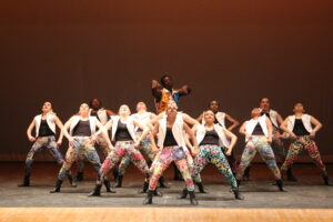 A large group of dancers perform hip hop on stage