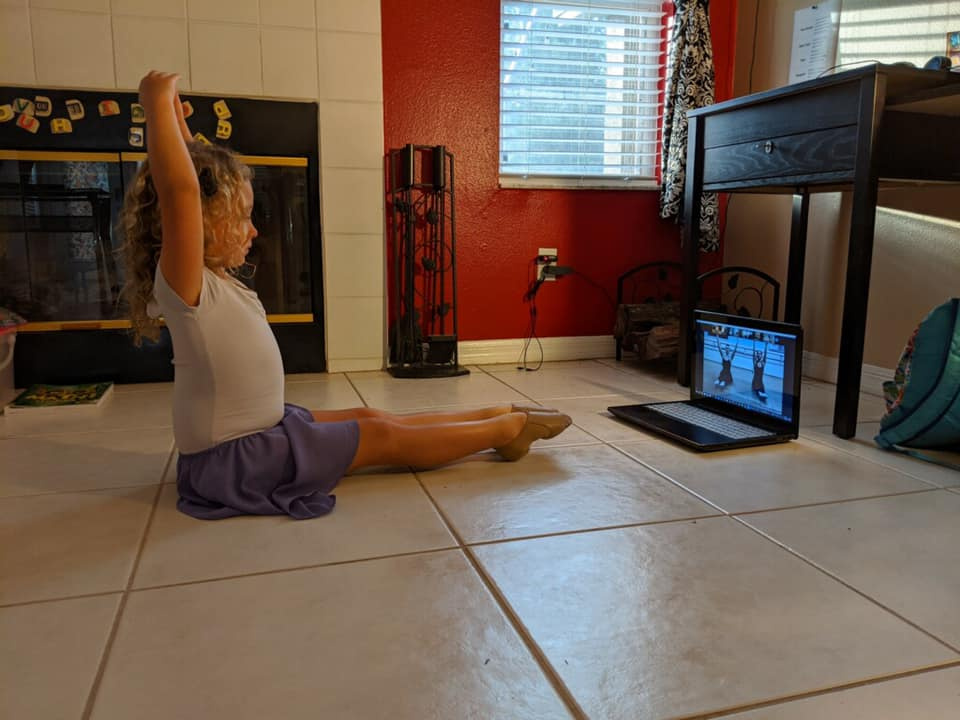 A young dancer taking a virtual class from home
