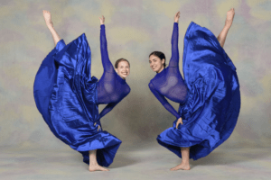 Two dancers doing leg extensions in large flowy skirts