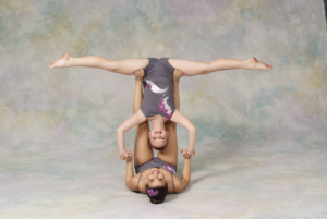 A dancer doing a split upside down while being based by another dancer
