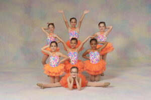 A group of young dancers pose in jazzy costumes