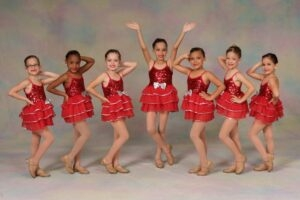Young dancers pose in red costumes and tap shoes