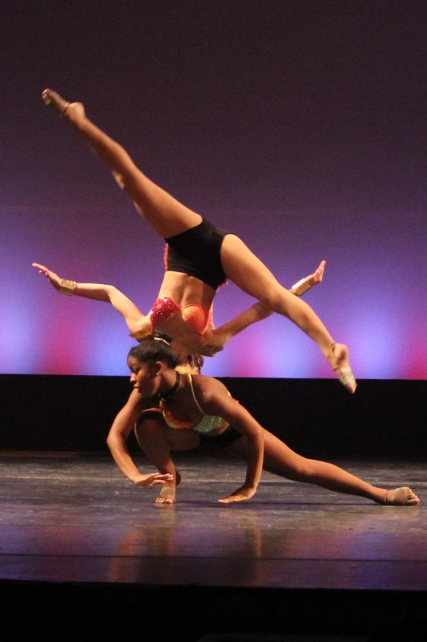Two dancers doing acrobatics on a stage