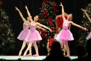 Ballerinas pose in tutus and pointe shoes on stage