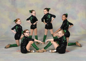 A small group of young dancers wearing tap shoes