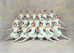 A group of ballet dancers smiling at the camera