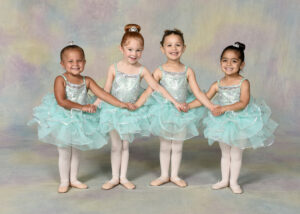 Four young ballerinas smile at the camera while holding hands